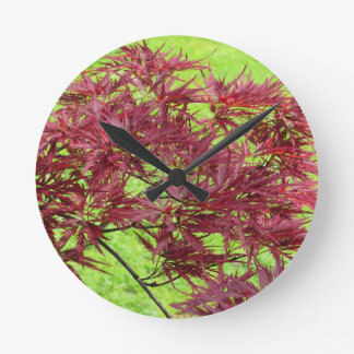 Red japanese maple leaves on green background round clock
