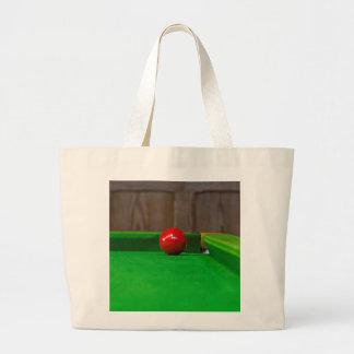 Red pool ball on pool table bag