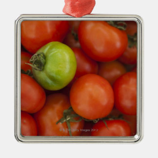 red tomatoes with one green one for sale at the christmas ornament