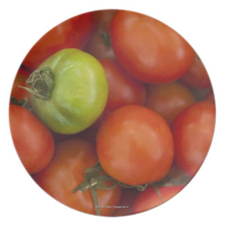 red tomatoes with one green one for sale at the plate
