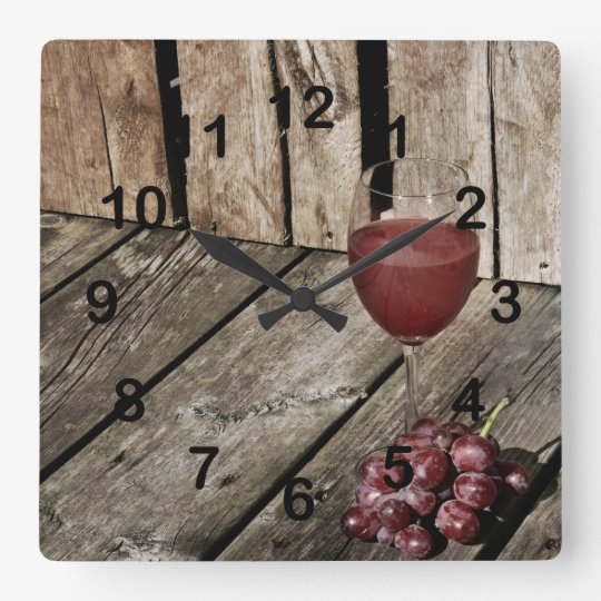 Red wine glass and grapes on wood texture