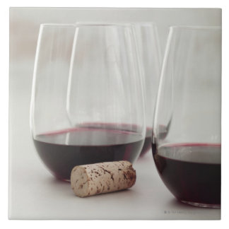 Red wine in stemless glasses tile