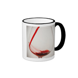 Red wine pouring into glass close-up coffee mug