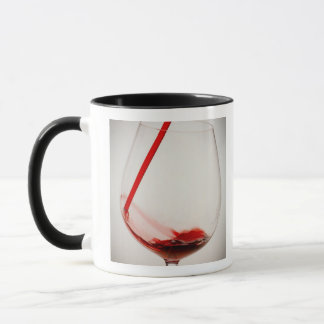 Red wine pouring into glass, close-up mug