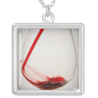 Red wine pouring into glass, close-up silver plated necklace
