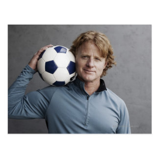 Redhead holding a soccer ball on his shoulder postcard