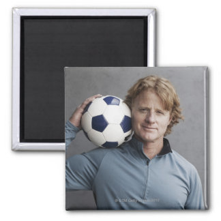 Redhead holding a soccer ball on his shoulder square magnet