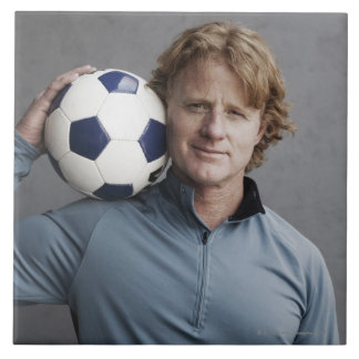 Redhead holding a soccer ball on his shoulder tile