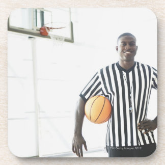 Referee holding basketball on court coaster