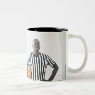 Referee holding basketball on court coffee mug