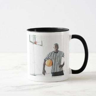 Referee holding basketball on court mug