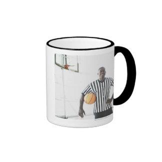 Referee holding basketball on court coffee mugs