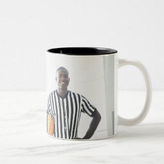 Referee holding basketball on court Two-Tone mug