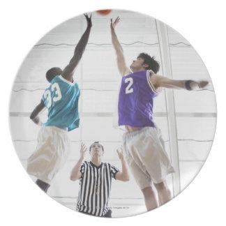 Referee watching basketball players jumping plate
