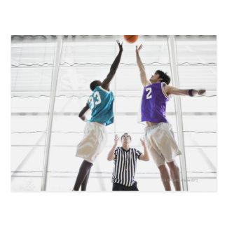 Referee watching basketball players jumping postcard