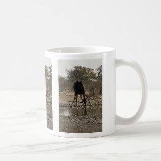 Reflected image of a drinking giraffe coffee mugs