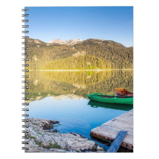 Reflection in water of mountain lakes and boats spiral notebook