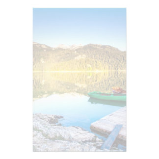 Reflection in water of mountain lakes and boats stationery