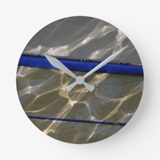 Reflections in the helmet of a fishing boat wall clock