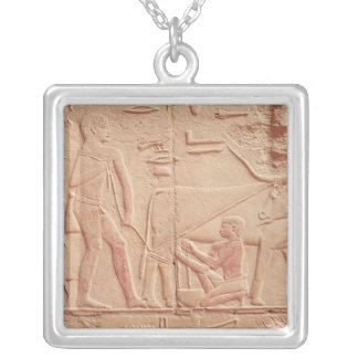 Relief depicting a man milking a cow silver plated necklace