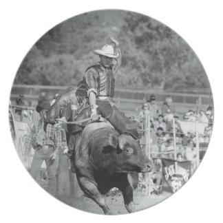 Rider hanging on to bucking bull 2 plate