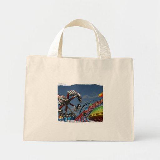 Rides at a county fair against a blue sky canvas bags
