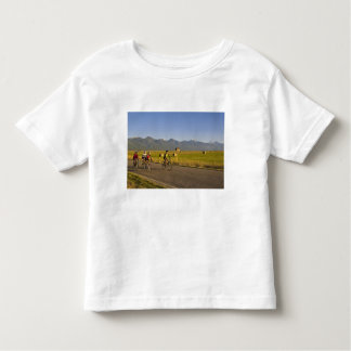 Road bicyclists ride down a back country road toddler T-Shirt