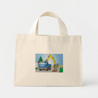 Road site with blue truck and yellow excavator mini tote bag