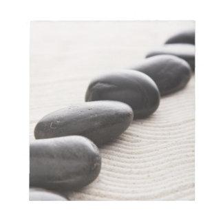 Rocks on sand notepad