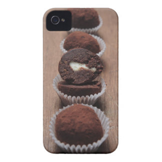 Row of chocolate truffles on wood iPhone 4 case