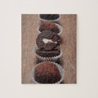 Row of chocolate truffles on wood jigsaw puzzle