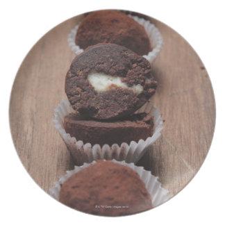 Row of chocolate truffles on wood plate