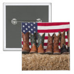 Row of cowboy boots on haystack buttons