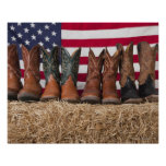 Row of cowboy boots on haystack poster