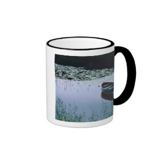 Rowboat on small lake surrounded by water coffee mug