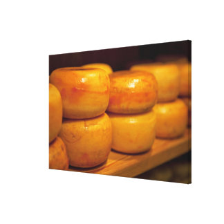 rows of colourful yellow Edam cheeses lined up Canvas Print