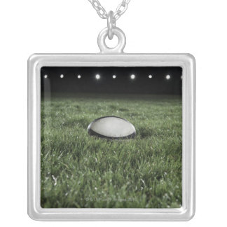 Rugby ball sitting on the grass pitch of a silver plated necklace