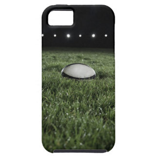 Rugby ball sitting on the grass pitch of a tough iPhone 5 case