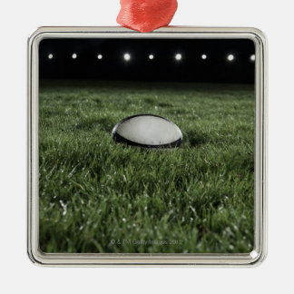 Rugby ball sitting on the grass pitch Silver-Colored square decoration