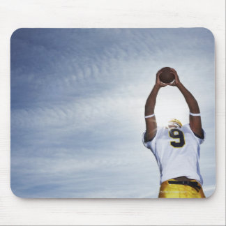 rugby player holding ball up with body stretched mouse mat
