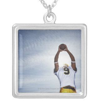 rugby player holding ball up with body stretched silver plated necklace