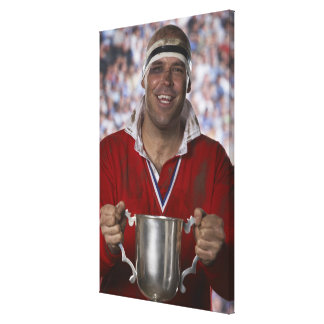 Rugby player holding trophy cup, portrait canvas print