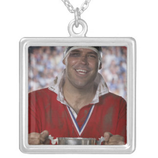 Rugby player holding trophy cup, portrait silver plated necklace