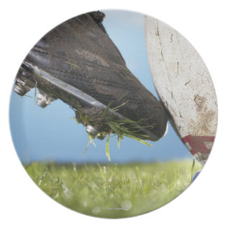 Rugby player kicking ball off tee, close up of plate