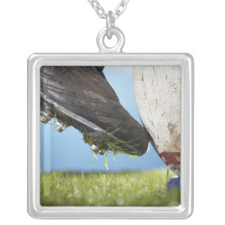 Rugby player kicking ball off tee, close up of silver plated necklace