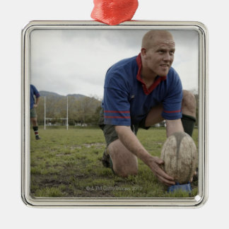 Rugby player positioning ball on rugby pitch ornament