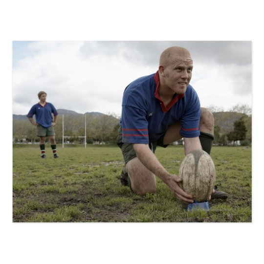 Rugby player positioning ball on rugby pitch postcard