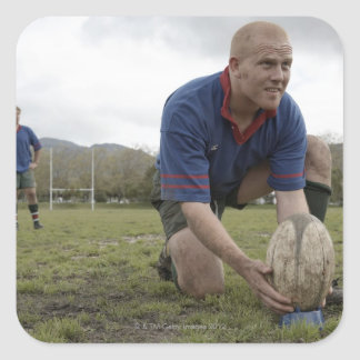 Rugby player positioning ball on rugby pitch square sticker