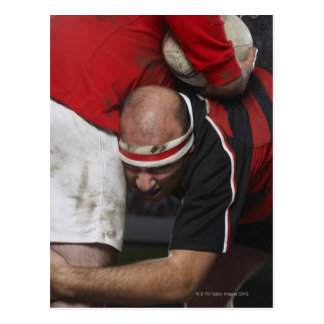 Rugby player tacking opponent, mid section postcard