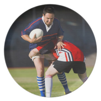 Rugby player tackling another plates